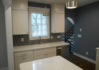 Renovated kitchen with white cabinets and modern stairwell. This house was renovated after a fire damage.