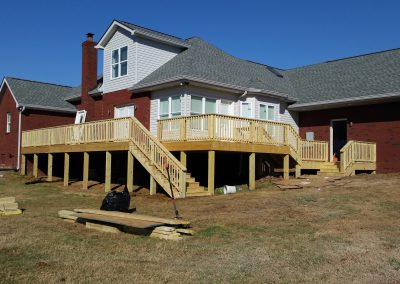 Deck and back side of a brick house rebuilt after being destroyed by a fire